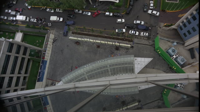 high angle down birdseye pov of multi-story office buildingor hotel with glass windows and flags. pedestrians on street, cars parked below. could be suicide pov. - stockwerk stock-videos und b-roll-filmmaterial