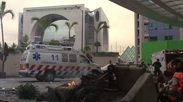 "wide angle of paramedics, firemen, and police helping injured people from explosion, accident, or fire. paramedics carry man on stretcher or gurney. ambulance labeled ""urgencias"". palm trees, modern building, and green screen in background. calakmul coron - paramedic stock videos & royalty-free footage"
