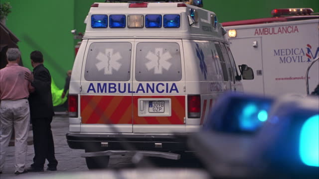 "wide angle of paramedics, police officers, and firemen helping injured people against green screen. paramedic shuts backdoor of ambulance  labeled ""ambulancia"". could be for explosion, emergency, accident, or fire. license plate of spain. europe. bizbars. - spain stock videos & royalty-free footage"