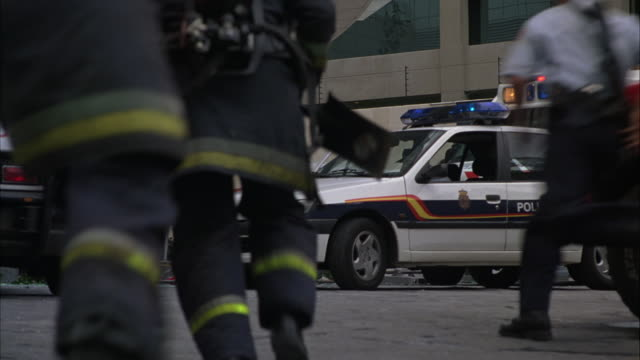 wide angle of police officers and paramedics helping injured people. firemen run with fire extinguishers towards multi-story building. mercedes ambulances and police cars with bizbars visible. us or american officer with us flag on uniform helped by polic - hospital trolley stock videos & royalty-free footage