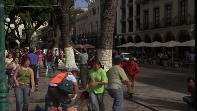 PAN LEFT TO RIGHT OF PEOPLE RUNNING ON SIDEWALK OR PEDESTRIAN PLAZA DOWN CITY STREET IN EUROPE OR MEXICO CITY. SECURITY GUARDS AND POLICE OFFICERS WAVING AND MOTIONING WITH HANDS. PANIC REACTION EMERGENCY, EVACUATION, OR DISASTER EVENT. PAN RIGHT TO CHEVR