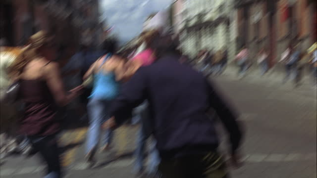 hand held of crowd of people running on cobblestone city side street in europe or mexico city. people begin pushing and shoving each other. panic reaction to emergency, disaster, or evacuation. police officers or security guards visible running through cr - evacuazione video stock e b–roll