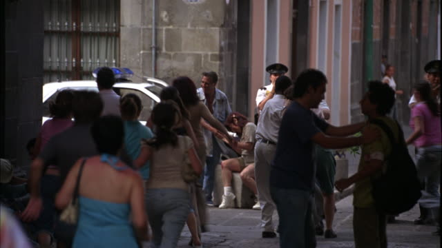 wide angle of crowd of people running down alley or side street in europe or mexico city. chevrolet astra police car with flashing bizbar lights in bg. could be panic reaction to emergency or evacuation. wounded or injured person being helped by other ped - evacuazione video stock e b–roll