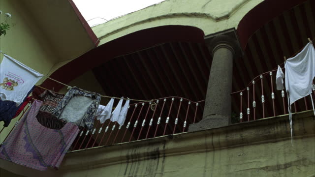 up angle of second-story railing in courtyard of lower class apartment building or residence. clothesline and column visible. could be europe, middle east, or mexico city. - {{ contactusnotification.cta }} stock-videos und b-roll-filmmaterial