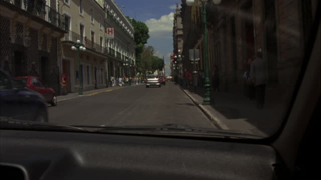 vídeos de stock, filmes e b-roll de hand held driving pov through traffic on cobblestone city street in europe or mexico city. see rear windshield and bumper of speeding chevrolet astra car coupe or hatchback as it slams on brakes, comes to complete stop, then turns and accelerates down str - sony pictures entertainment