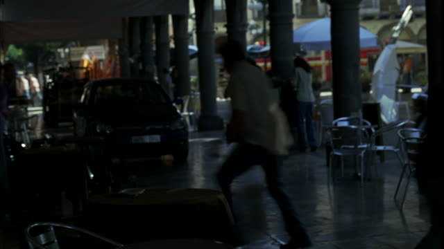 hand held of pedestrians, shoppers, or tourists on covered sidewalk near outdoor cafe in europe. people turning and running out of way when chevrolet astra hatchback speeds onto sidewalk, knocking over tables, umbrellas, and chairs. could be high-speed ch - {{ contactusnotification.cta }} stock-videos und b-roll-filmmaterial