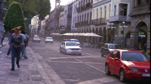 """vídeos de stock, filmes e b-roll de hand held of high-speed police chase between """"policia local"""" chevrolet astra with bizbar flashing lights and second, unmarked astra hatchback. pedestrians in plaza or tourist shopping area move away from cobblestone city street. people appear agitated. re - sony pictures entertainment"""
