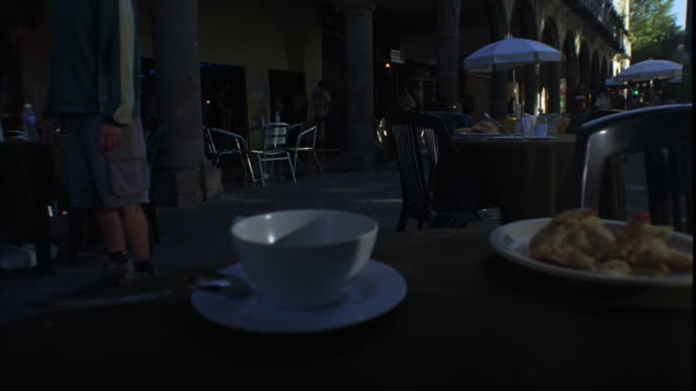 vídeos de stock, filmes e b-roll de medium angle of edge of table in outdoor cafe near covered sidewalk. umbrellas and chairs. people in bg appear agitated or frantic. coffee cup in fg. - sony pictures entertainment