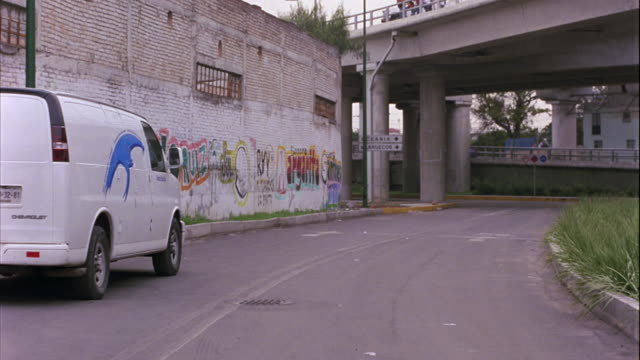 hand held moving pov of freeway and highway overpasses near walls covered with graffiti. forward view from car or truck. inner city, rundown slums or urban area. spanish and arabic writing on walls. europe, middle east, or mexico city. - graffito stock-videos und b-roll-filmmaterial