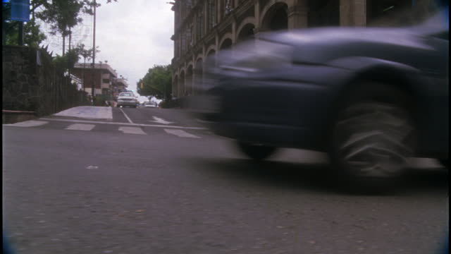 """pan up from intersection of european city street where chevrolet astra """"policia local"""" police car speeds around the corner, followed by a second, unmarked astra. police and car chases. renaissance architecture stone buildings. oncoming cars and traffic ve - evacuation stock videos & royalty-free footage"""