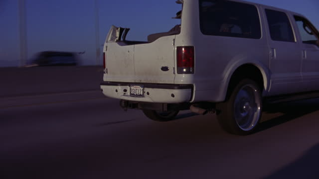 vídeos de stock, filmes e b-roll de wide angle moving pov 3/4 left forward of white suv, ford excursion, or speeding car with half blown roof driving on highway or 105 freeway. - sony pictures entertainment