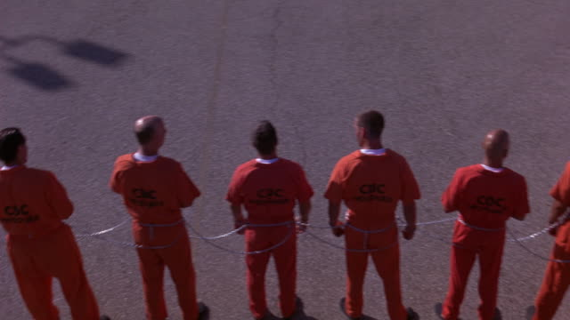 """stockvideo's en b-roll-footage met high angle down of prisoners, inmates, or chained men in orange jumpsuits labeled """"cdc prisoner"""" standing in a line. could be for jail, prison, penitentiary. - gevangene"""