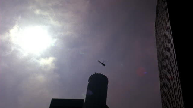 up angle of news or police helicopter flying over us bank tower in downtown los angeles. skyscrapers and high rises office buildings. - us bank tower stock videos & royalty-free footage