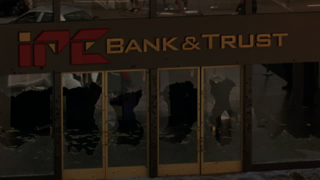 """hand held of snipers or swat team police officers with rifles positioned on rooftop of """"ipe bank & trust,"""" aiming below where police stand-off occurs. gunshots on police cars as officers dive behind. gunmen inside bank. could be bank robbery. police actio - armed police forces stock videos & royalty-free footage"""