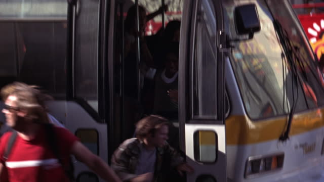 vídeos de stock, filmes e b-roll de hand held of people running off los angeles city bus and onto sidewalks of city street where pedestrians also begin running. could be panic or reaction. - sony pictures entertainment