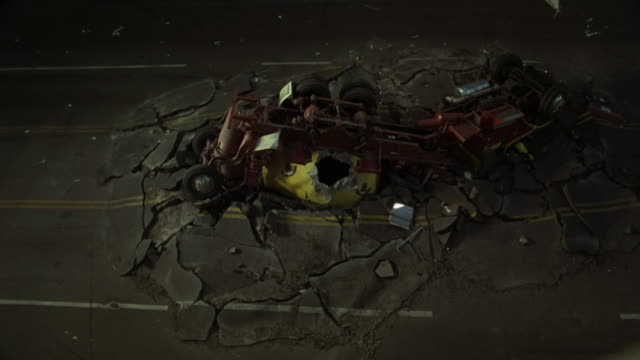 vídeos de stock, filmes e b-roll de high angle down of crashed semi truck in middle of city street. surrounded by broken concrete and rubble as if dropped from above. - sony pictures entertainment
