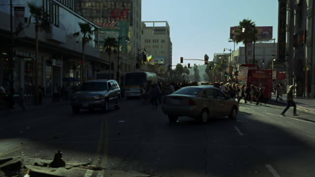 hand held of pedestrians and people running through city streets near graumans chinese theatre on sunset strip. rubble and demolished concrete surrounding overturned semi truck that appears to have crashed or been dropped.  city buses and cars stopped in - rubble stock-videos und b-roll-filmmaterial
