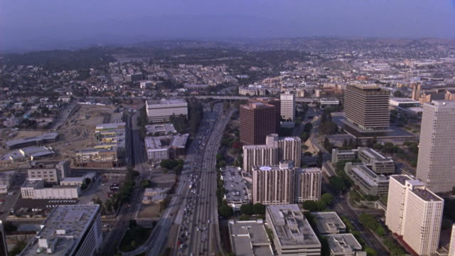 vídeos de stock, filmes e b-roll de aerial of office buildings near downtown next to a freeway, interstate, or highway. - sony pictures entertainment