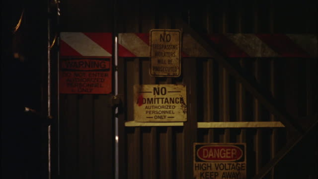 """MEDIUM ANGLE OF WALL OF CORRUGATED METAL WITH """"NO ADMITTANCE"""" SIGN, ALSO """"DANGER HIGH VOLTAGE"""" IN SUBWAY TUNNEL."""