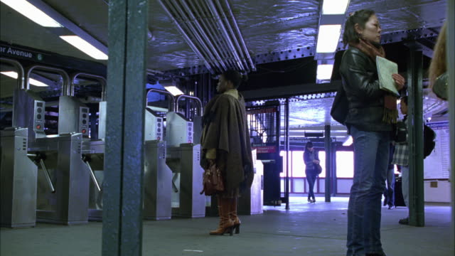 wide angle of elder avenue subway station in the bronx. railway. passengers, people entering turnstiles. - 自動改札機点の映像素材/bロール