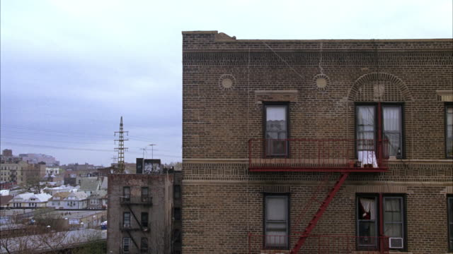 wide angle of side of lower class multi-story brick apartment building in queens. fire escape. urban area. - fire escape stock videos and b-roll footage