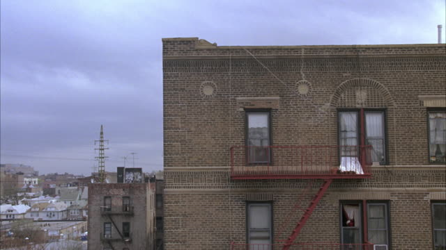 pan right to left from side of lower class multi-story brick apartment building in queens to subway train on aerial tracks. 61st and woodside station. fire escape. urban area. - fire escape stock videos and b-roll footage