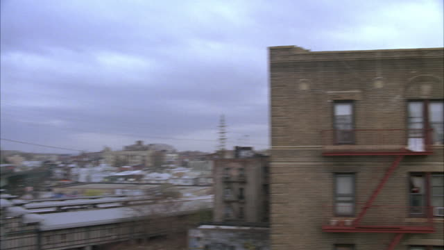 pan left to right from subway train on elevated tracks at station to side of lower class multi-story brick apartment building in queens to. 61st and woodside station. fire escape. urban area. - fire escape stock videos and b-roll footage