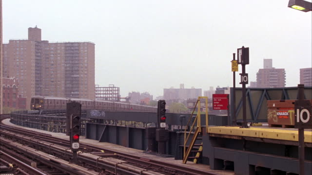 wide angle of a subway platform on elevated railway tracks in brooklyn.  subway light signal with red light on visible in fg. multi-story apartment buildings in bg. a subway train moves towards camera and passes platform. - railway signal stock videos & royalty-free footage