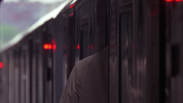 vídeos de stock, filmes e b-roll de medium angle of men in business suits walking through doors of subway cars. man in tan jacket stands in threshold of doorway, preventing the doors from closing. - sony pictures entertainment