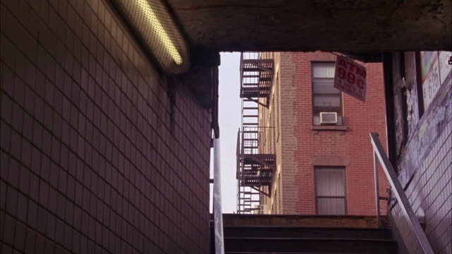 """medium angle from bottom of staircase, could be entrance to subway station. tiled walls on both sides of stairs. brick multi-story apartment building with fire escape on side of building visible at top of stairs. sign reading """"atm 99 cents"""" hanging at ent - fire escape stock videos & royalty-free footage"""