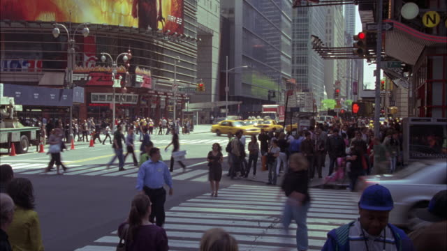 WIDE ANGLE RAPID TIME LAPSE OF PEOPLE, PEDESTRIANS WALKING ON SIDEWALKS AND CROSSING INTERSECTION OF 42ND STREET AND BROADWAY IN TIMES SQUARE, NEW YORK. BILLBOARDS HANG ON SIDES OF MULTI-STORY AND HIGH RISE BUILDINGS. CARS, TAXIS DRIVING THROUGH INTERSECT