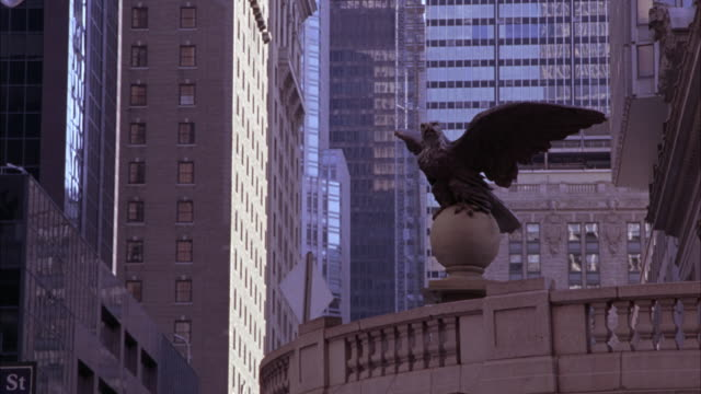 MEDIUM ANGLE OF BRONZE OR METAL EAGLE SCULPTURE ABOVE ENTRANCE TO GRAND CENTRAL STATION IN MIDTOWN MANHATTAN, NEW YORK. HIGH RISE AND SKYSCRAPER OFFICE OR APARTMENT BUILDINGS IN BG.