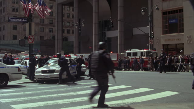 wide angle of police cars with bizbars, flashing lights and fire trucks stopped on the corner of 42nd street and vanderbilt ave in front of entrance to grand central station in midtown manhattan, new york. police officers, cops and swat team members gathe - station stock-videos und b-roll-filmmaterial
