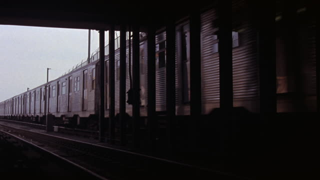vídeos de stock, filmes e b-roll de wide angle of subway train exiting underground tunnel. could be metro rail, commuter train, f-train, or rapid transit line. factory or industrial area in bg. brick wall topped with barbed wire. lower class area. rundown. - tunnel