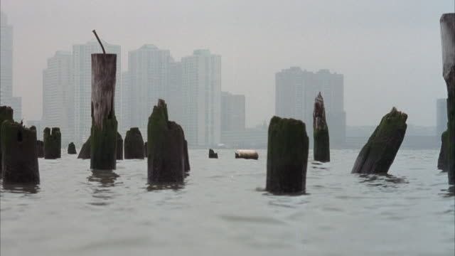medium shot inside water of broken wooden logs or pilings coming out of the water. skyline in the faint bg. foggy, overcast day. water rises and blocks shot periodically. could in east river. pans back and forth of logs. see what looks like a buoy or barr - {{ contactusnotification.cta }} stock videos & royalty-free footage