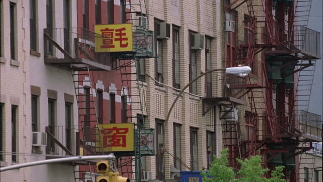 est medium angle of sign with chinese characters on side of multi-story buildings. see fire escapes on side of buildings. - 非常階段点の映像素材/bロール