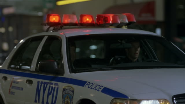 medium angle. front side view of nypd cop car with sirens on as police car drives past cars on city street. police chase. gun fires at front right headlights and police car swerves off screen. shot pans down to front of car then street. - police car stock videos & royalty-free footage