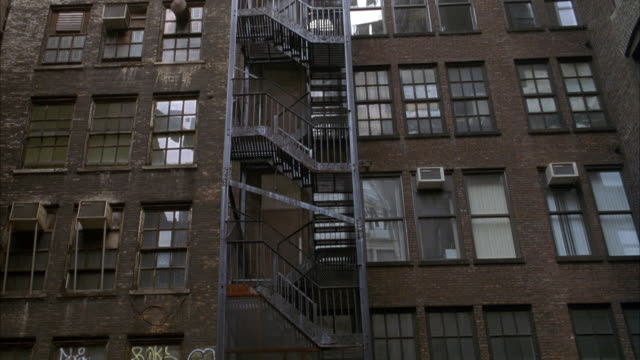 wide angle of brick apartment buildings. fire escape, stairs. pan up to clothes on clotheslines hanging across buildings. man falls from above. stunts. cables holding stuntman visible. lower class. - fire escape stock videos and b-roll footage