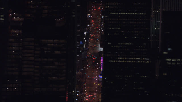 aerial of cars and taxis with headlights on sixth avenue or city street, passing new york landmark radio city music hall, between skyscrapers or multi-story buildings in midtown manhattan. - {{ contactusnotification.cta }} stock-videos und b-roll-filmmaterial