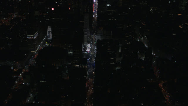 aerial birdseye pov of cars and taxis with headlights on city streets of midtown manhattan. follows broadway into new york landmark times square. skyscrapers or multi-story buildings on city blocks in theater district. - manhattan theater district stock videos and b-roll footage