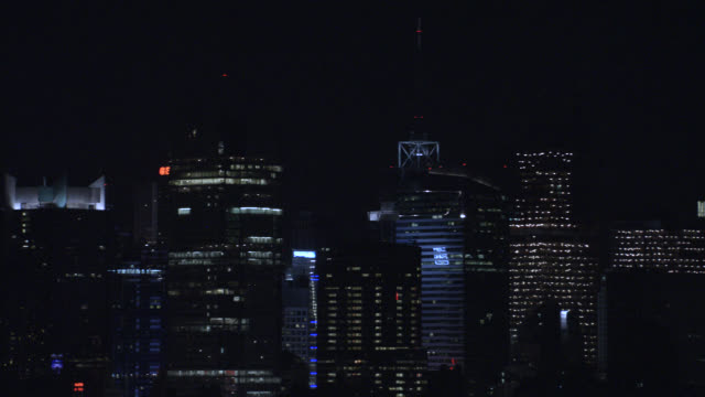 aerial of orange quarter moon over new york city skyline or manhattan cityscape. midtown multi-story buildings and skyscrapers with lights include chrysler building, citigroup center, worldwide plaza, new yorker hotel, ge building and metlife building. - citigroup center manhattan stock videos & royalty-free footage