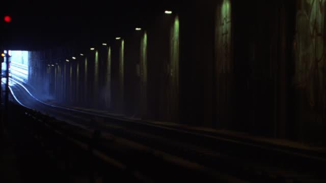 vídeos de stock, filmes e b-roll de medium angle of subway train entering tunnel. railway tracks. graffiti on wall in bg. - tunnel