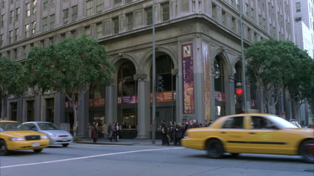 est wide angle shot of multiple level high rise hotel or office building at the corner of city street intersection as cars and taxis drive by, with business men and women walk by. see group of pedestrians gather across street. - level stock videos and b-roll footage