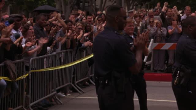 vídeos y material grabado en eventos de stock de hand held crowd of reporters and people clapping behind fence and police tape. microphones and cameras. could play for red carpet event. - cámara en mano