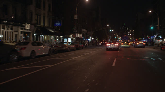 vídeos de stock, filmes e b-roll de process plate 1/4 left front driving pov through traffic in new york city streets. taxi cabs and other cars passing bars and restaurants, pedestrians and multi-story buildings. urban areas and inner cities. - placa de processo