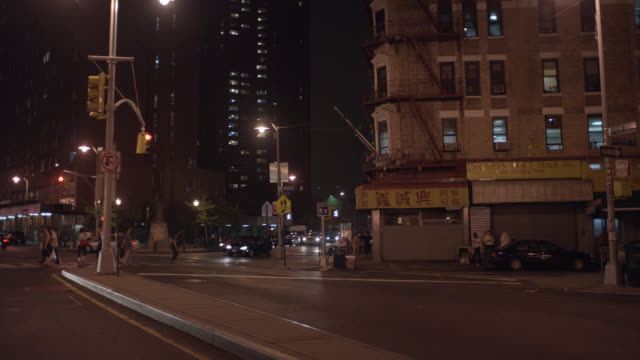 wide angle  of street corner in chinatown. cars and taxis with headlights pass on new york city streets and through intersection. - {{ contactusnotification.cta }} stock-videos und b-roll-filmmaterial