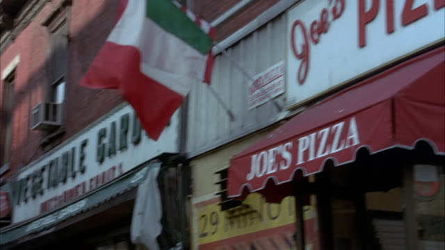 "medium up angle of storefront signs. see ""joe's pizza and vegetable garden"". shot pans back and forth of signs. italian flag outside of joe's pizza. - italian flag stock videos and b-roll footage"