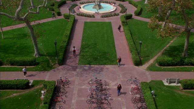 vídeos de stock, filmes e b-roll de pan up from bicycles on racks, past the youth triumphant or the four cornerstones of american democracy fountain, to bovard auditorium at the university of southern california, usc. college campuses, private schools. brick buildings. theaters. courtyard w - auditório