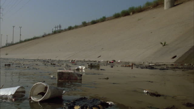 wide angle of trash or garbage in water of the los angeles river. pollution. amtrak train passes by in bg. police car with flashing lights on bizbar drives by. could be part of car chase. - inquinamento dell'acqua video stock e b–roll