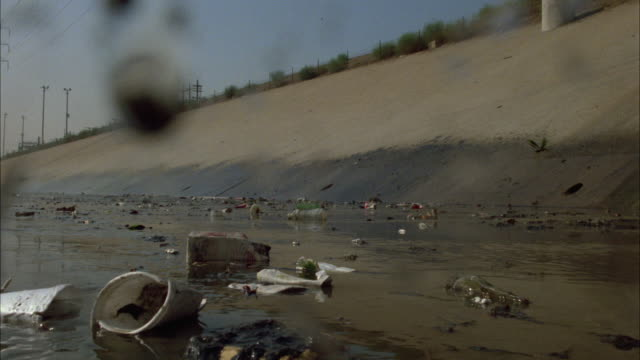 wide angle of trash or garbage in water of the los angeles river. pollution. amtrak train passes by in bg. police car with flashing lights on bizbar drives by. could be part of car chase. - water pollution stock videos & royalty-free footage